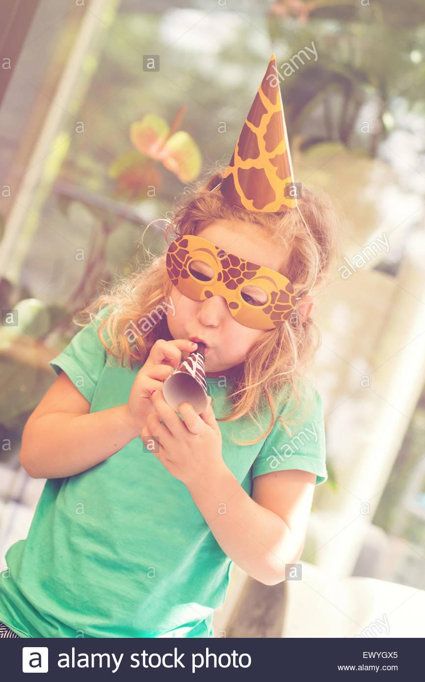 La ragazza di una maschera ad una festa di compleanno con una festa il ventilatore Immagini Stock