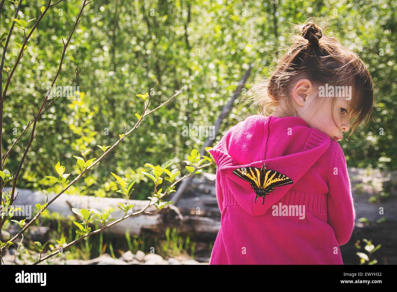 Ragazza giovane con una farfalla sulla sua schiena Immagini Stock