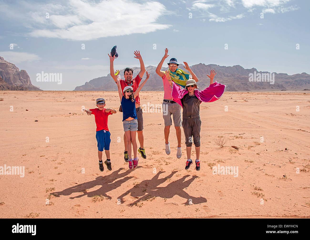 La famiglia felice del salto in aria di Wadi Rum, Aqaba Giordania Immagini Stock