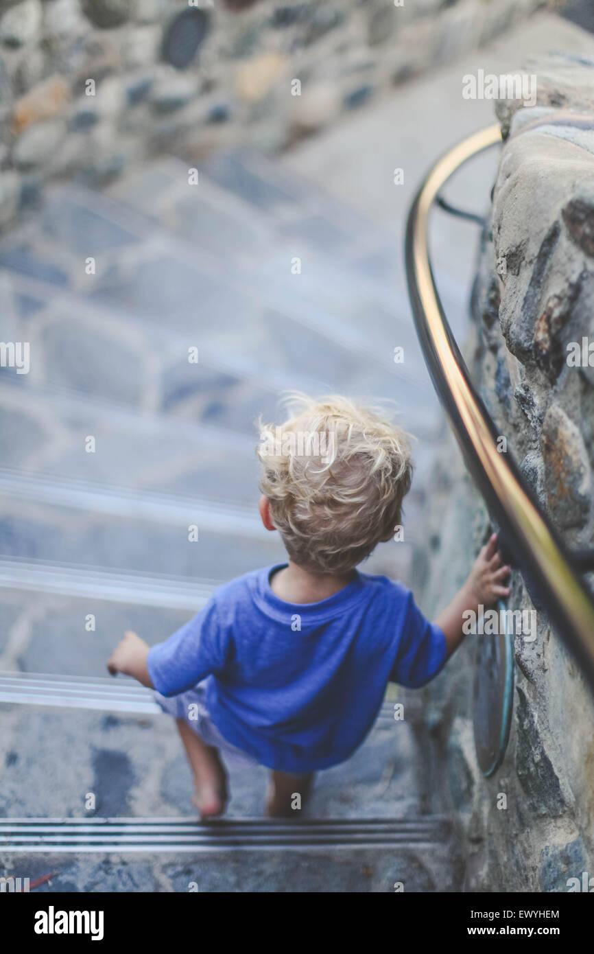 Vista posteriore del ragazzo a piedi giù per le scale Immagini Stock