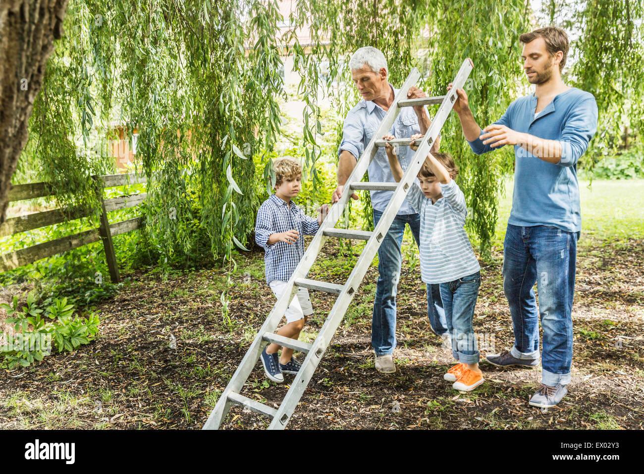 Uomo maturo con figlio scaletta di sollevamento con nipoti in giardino Immagini Stock