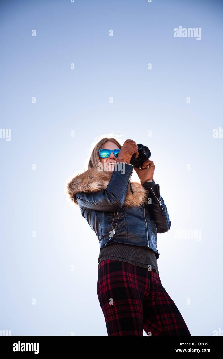 Angolo basso ritratto di donna fotografare contro il cielo blu Immagini Stock