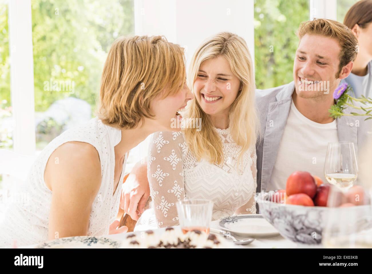 Famiglia adulti ridendo e spettegolare alla festa di compleanno Immagini Stock