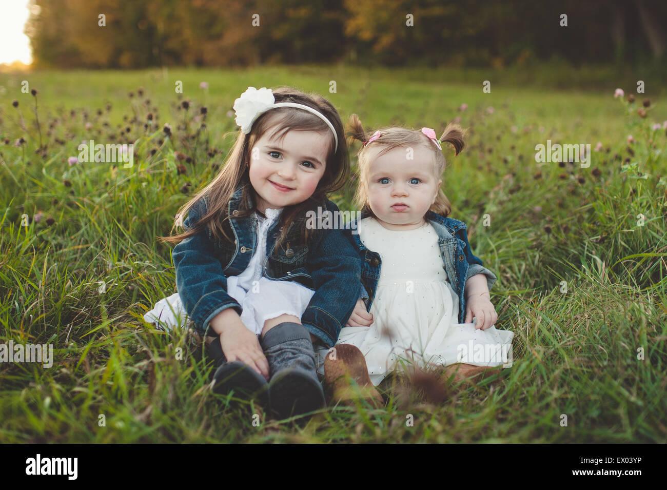 Ritratto di giovane ragazza e la sorella del bambino nel campo Immagini Stock