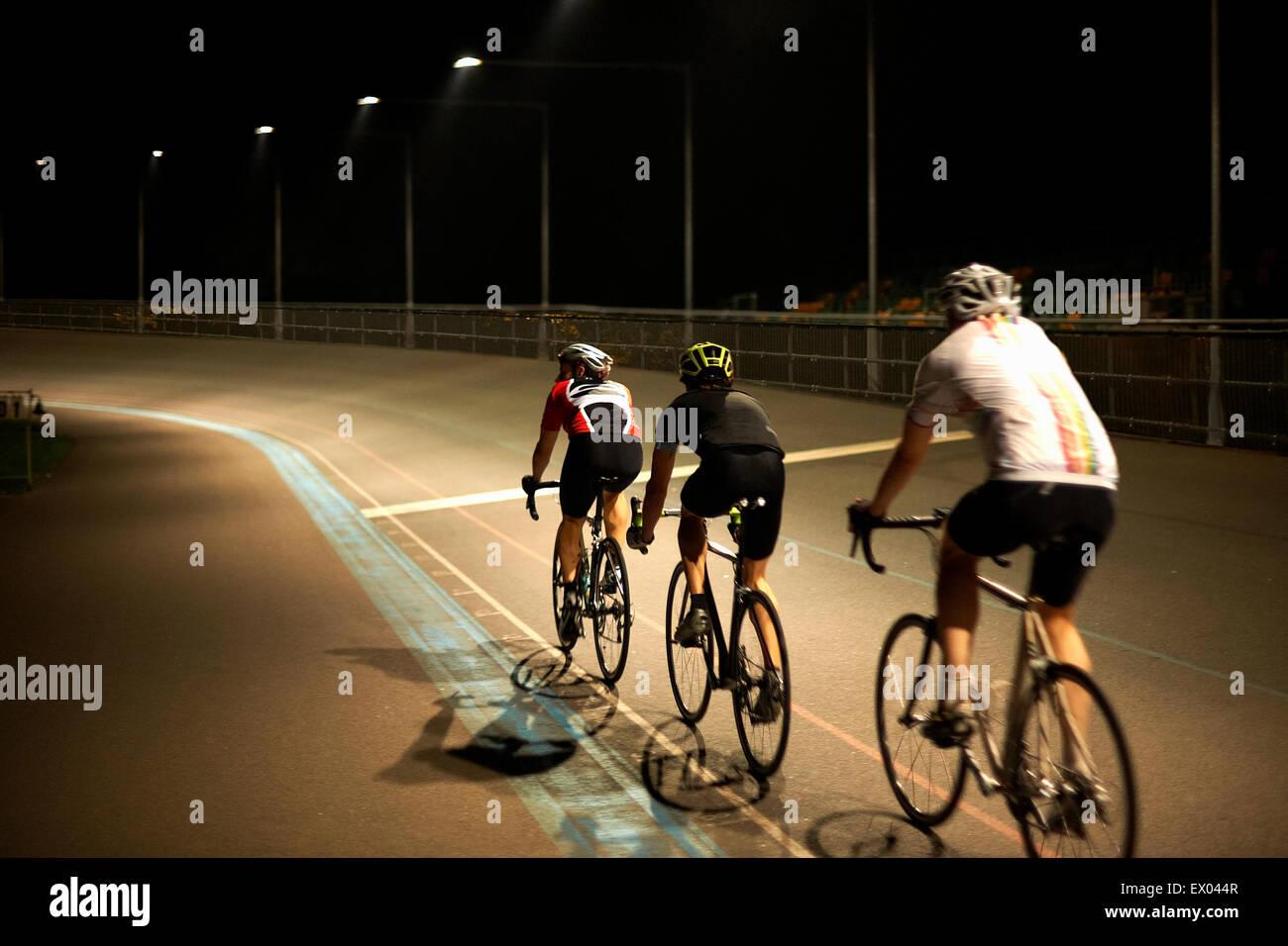 I ciclisti ciclismo su pista al velodromo, vista posteriore Immagini Stock