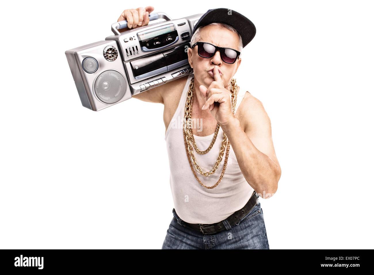 Uomo maturo in hip-hop vestiti portando un ghetto blaster sulla sua spalla e  tenendo un dito sulle sue labbra 1ab5d3f9e234