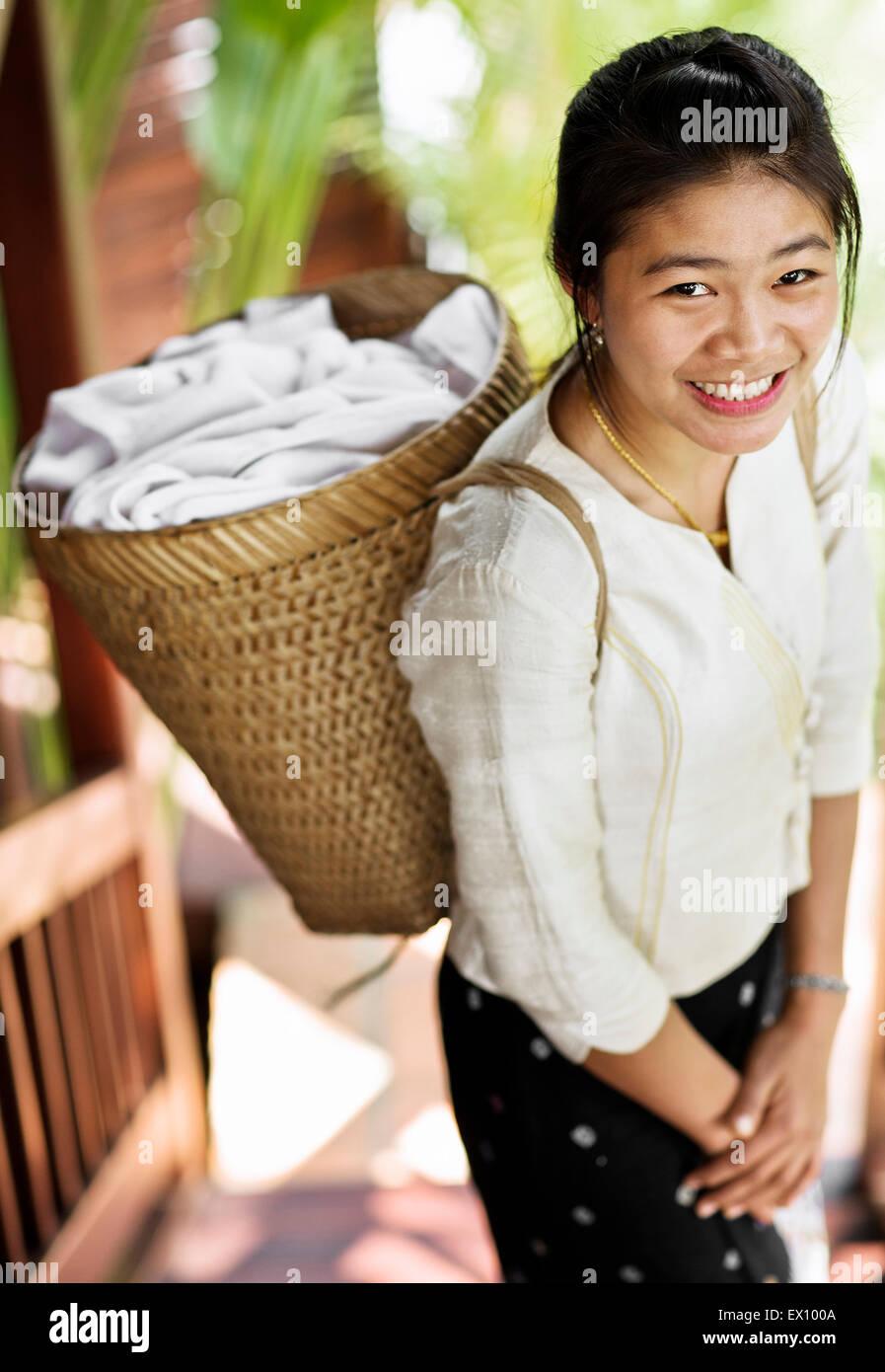 Una cameriera porta asciugamani in camera in un cestino sulla sua schiena a 3 Nagas da Alila Hotel. Luang Prabang, Immagini Stock