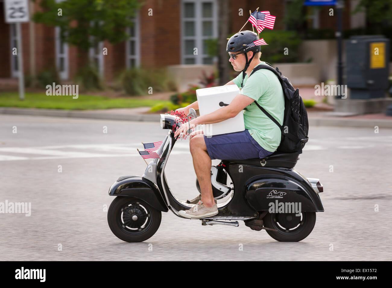 Un uomo che porta un raffreddatore sul suo scooter rides decorate con bandierine americane durante il Daniel Isola Immagini Stock