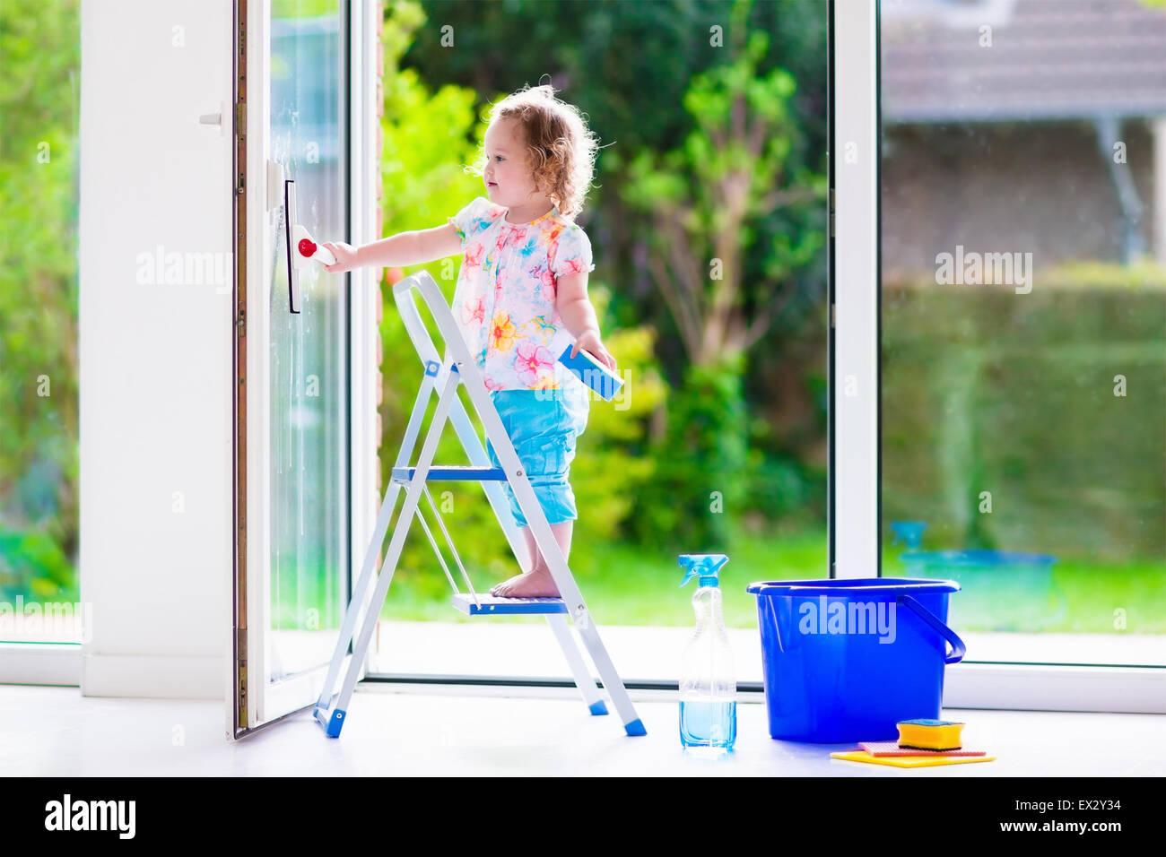 Bambina il lavaggio di una finestra. Kids pulire la casa. Aiutare i bambini a casa. Il Toddler kid la pulizia di Immagini Stock