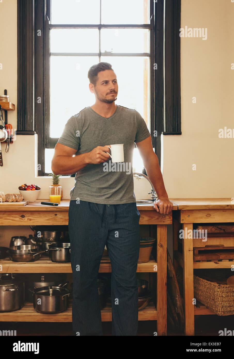 Ritratto di uomo in piedi in cucina tenendo una tazza di caffè guardando lontano nel pensiero. Rilassata giovane Immagini Stock