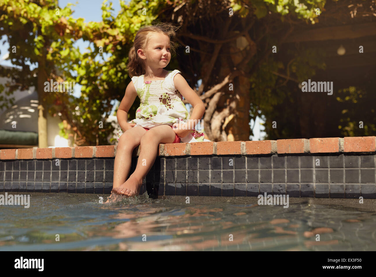 Colpo all'aperto di una bambina immergendo i suoi piedi nella piscina che guarda lontano. Incantevole piccola Immagini Stock