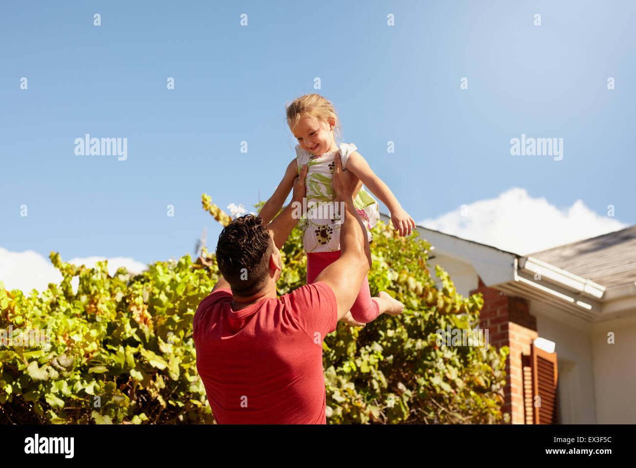 Giovane uomo il sollevamento di sua figlia in aria in alto. Felice padre e figlia a giocare nel loro cortile in Immagini Stock