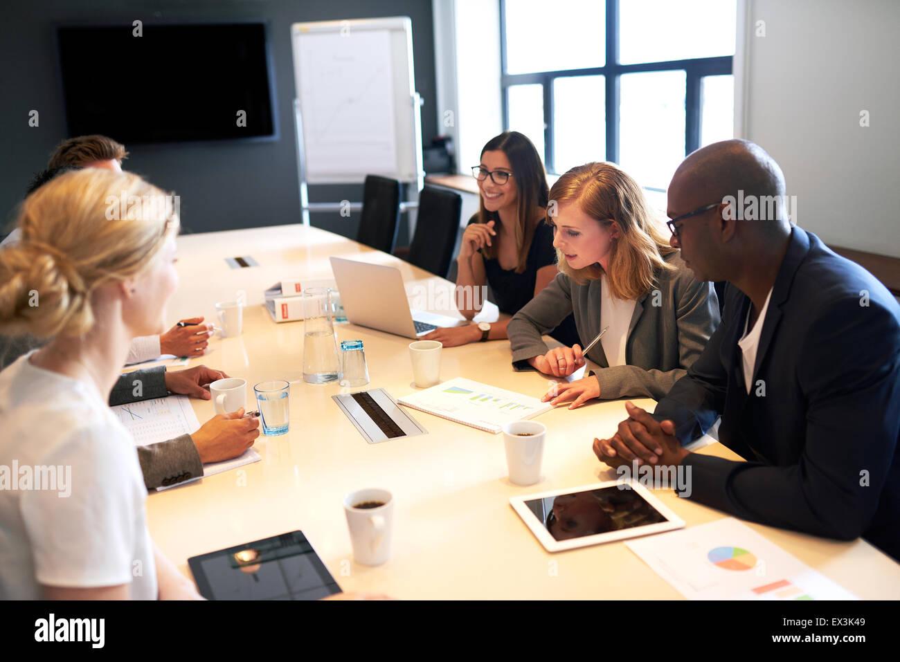 Un gruppo di giovani dirigenti tenendo una riunione in una sala conferenze Immagini Stock