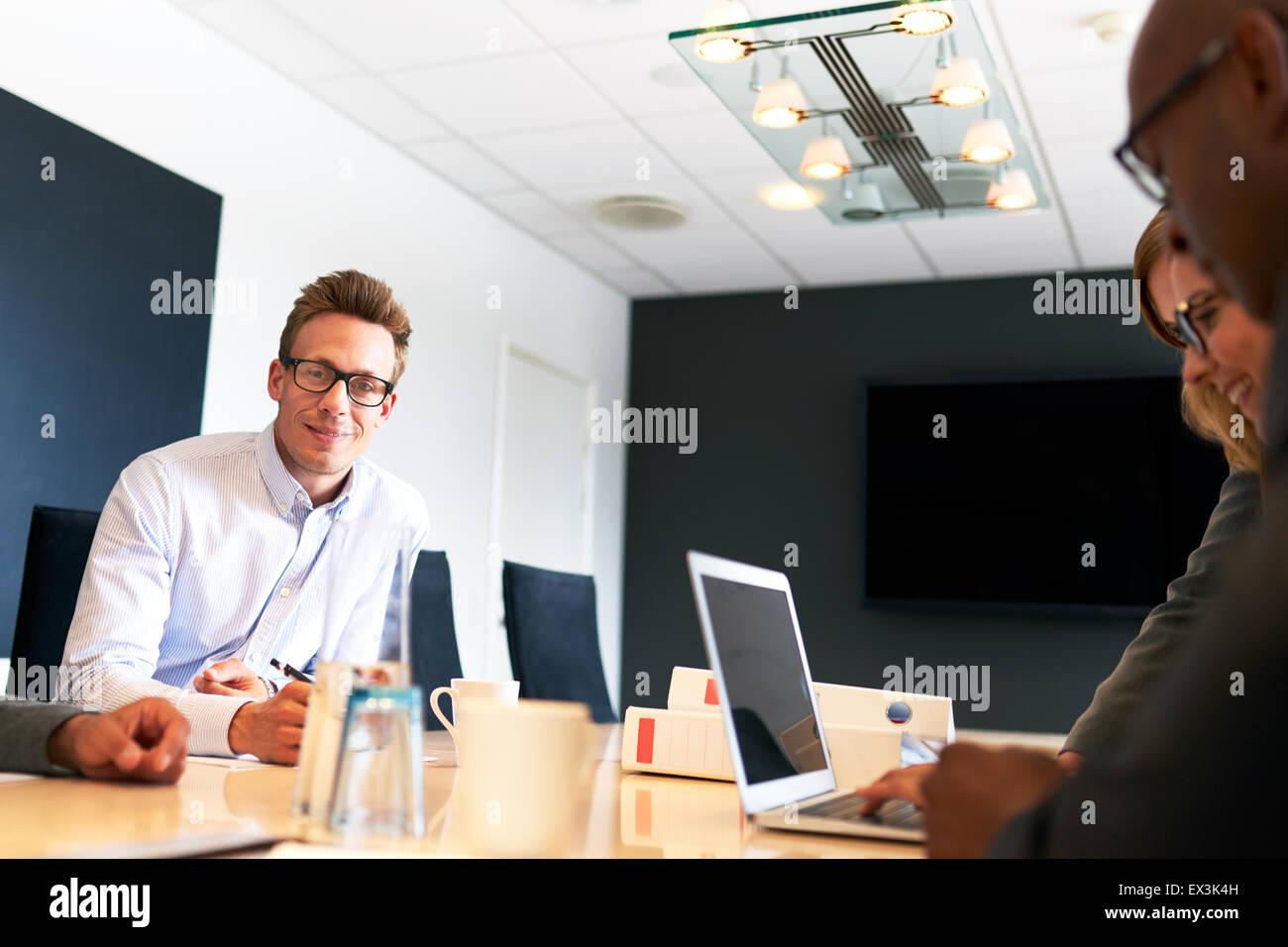 I giovani maschi bianchi sorride esecutivo a telecamera durante la riunione di lavoro. Immagini Stock