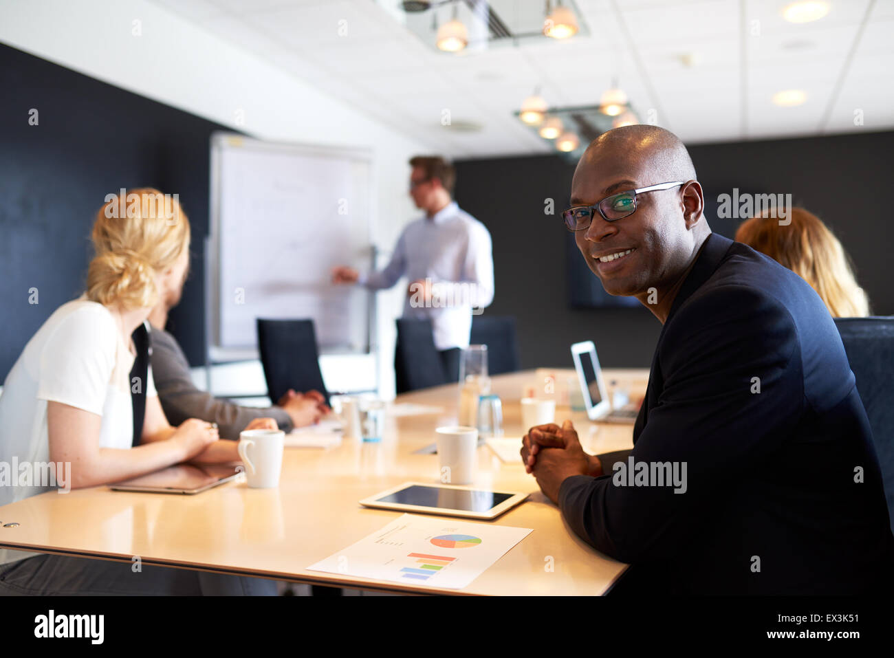 Maschio nero executive sorridente alla fotocamera durante una presentazione di lavoro Immagini Stock