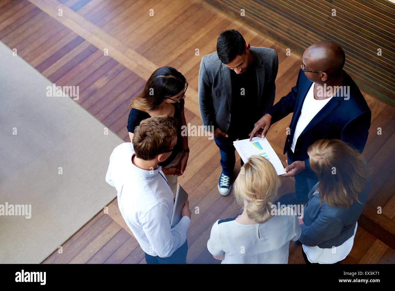 Vista guardando giù a colleghi in piedi in cerchio guardando i grafici sui documenti cartacei Immagini Stock
