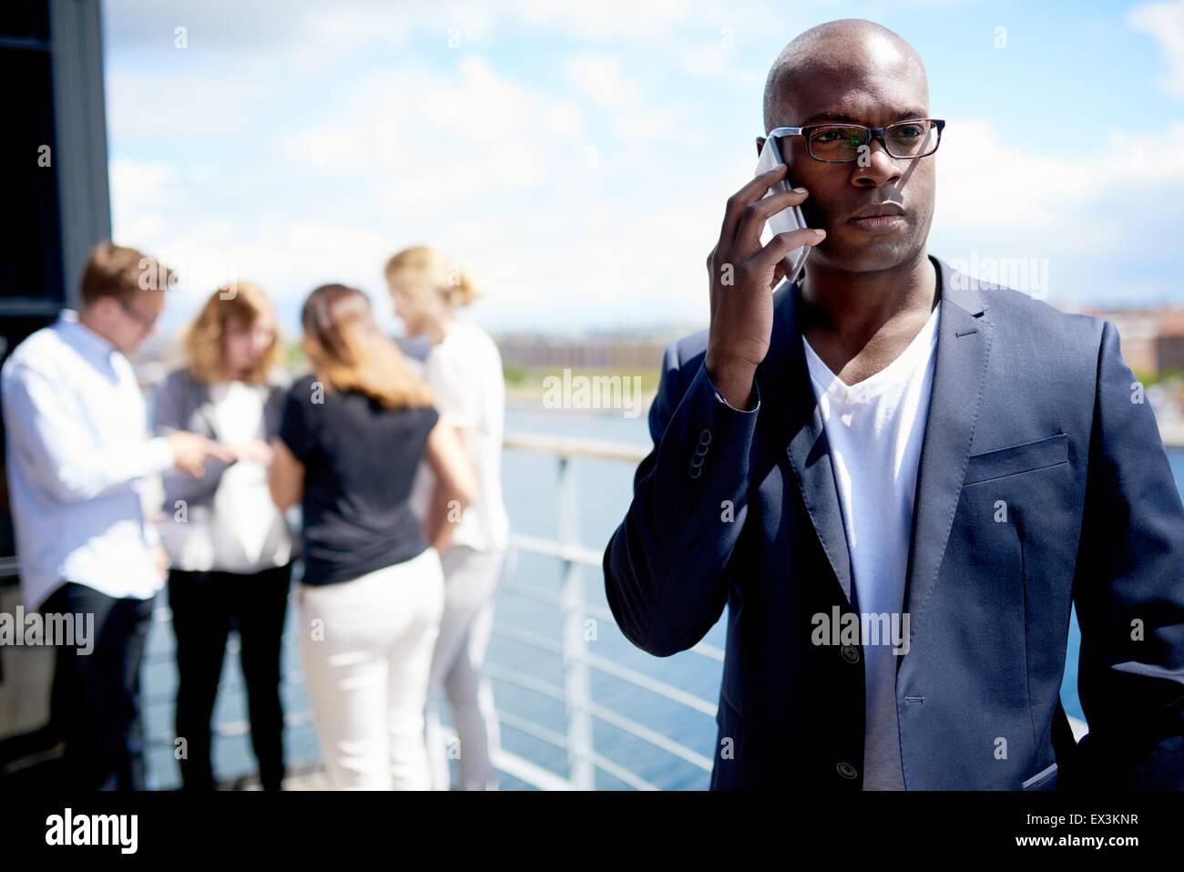 Maschio nero executive sul cellulare con i colleghi riuniti in background Immagini Stock