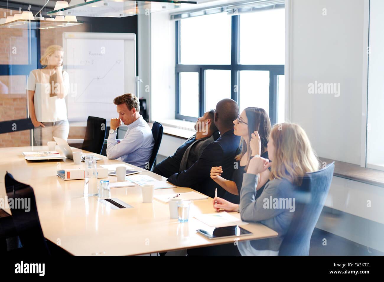 Femmina bianca executive in piedi alla testa della sala conferenze tabella conduce una riunione con i colleghi Immagini Stock