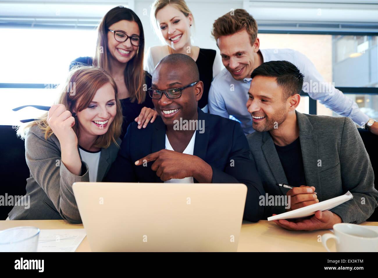 Maschio nero executive sorridente in telecamera con i colleghi riuniti intorno a lui e il computer portatile Immagini Stock