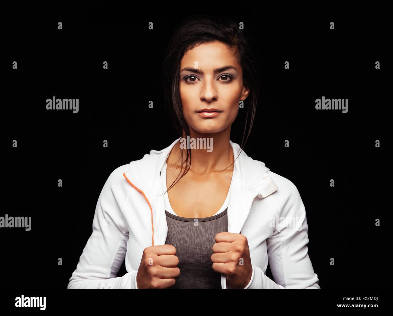 Colpo di giovani modello di fitness in posa di studio. Un sano giovane donna in abbigliamento sportivo in piedi Immagini Stock