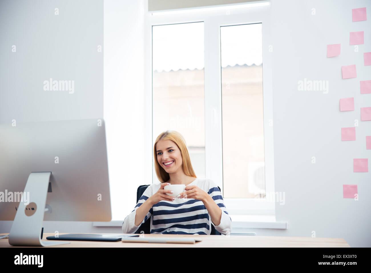 Donna sorridente photo editor di bere il caffè in ufficio Immagini Stock