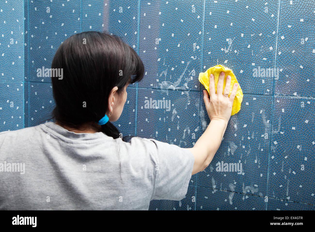 La donna in una maglietta grigio lava piastrelle blu con un panno