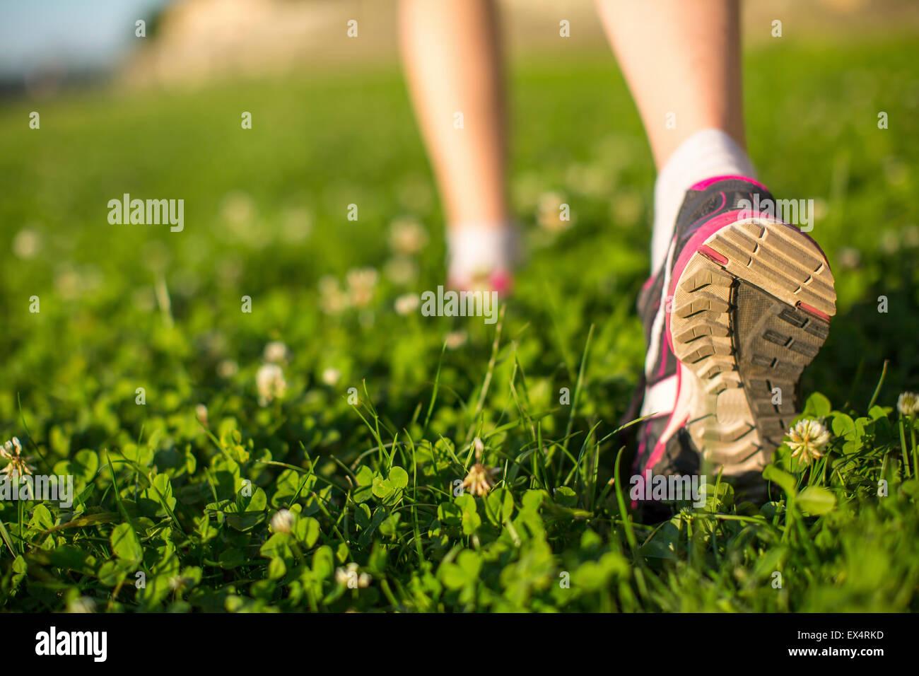 Gli escursionisti a piedi in erba verde all'aperto, angolo basso in prossimità del piede. Immagini Stock