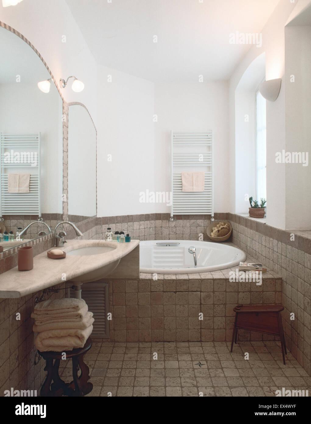 Vista interna del classico bagno con pavimento di piastrelle che si affaccia sulla vasca da bagno Immagini Stock