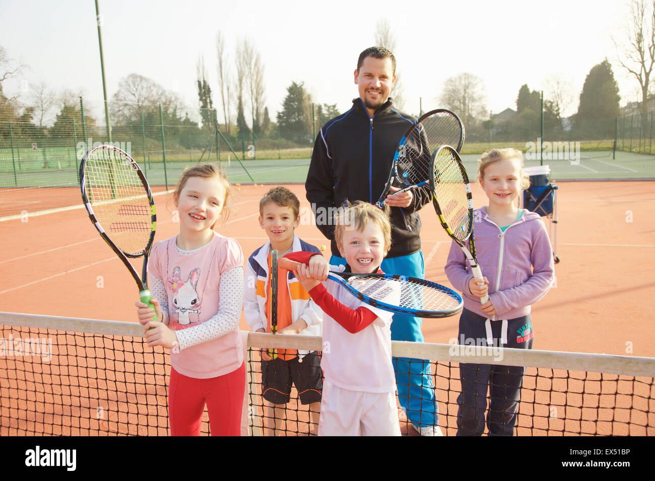 Ritratto di bambini e Coach sul campo da Tennis Foto Stock