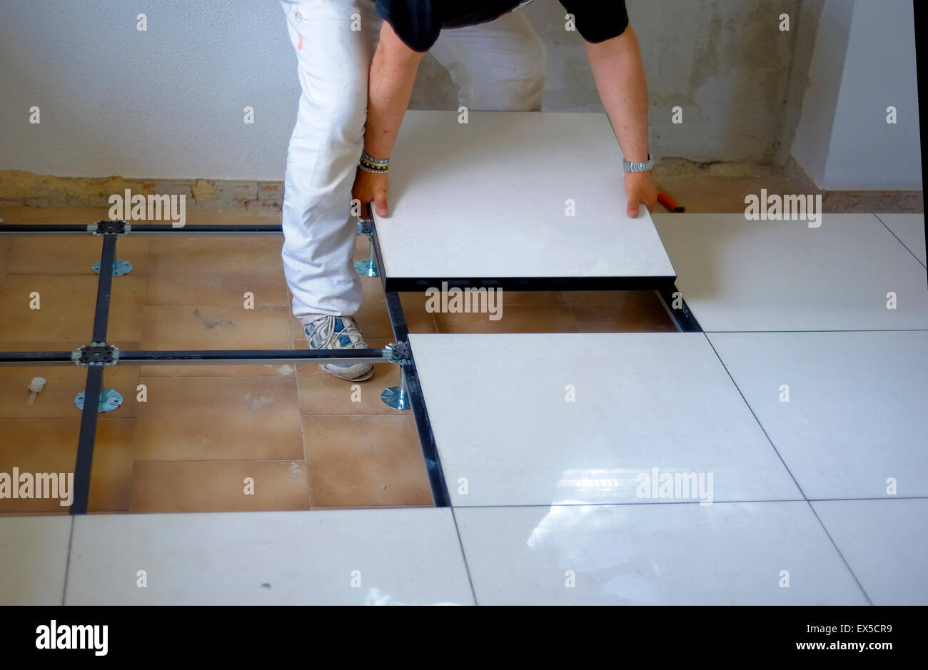 Lavoratore svolge un pavimento flottante su piedini in acciaio in