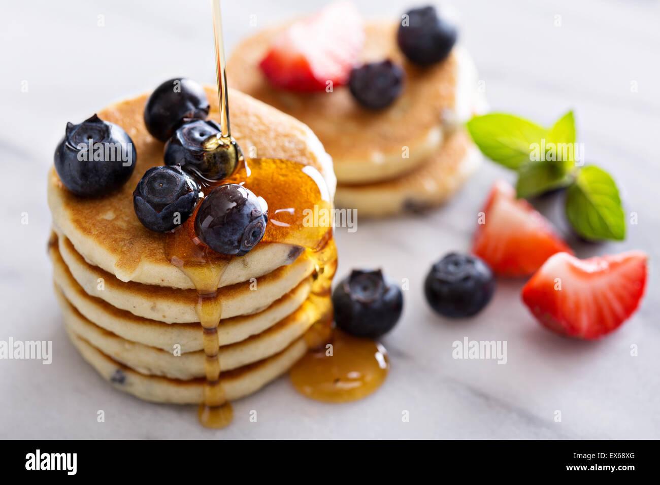 Pila di piccole pancake con bacche sulla scheda di marmo Immagini Stock