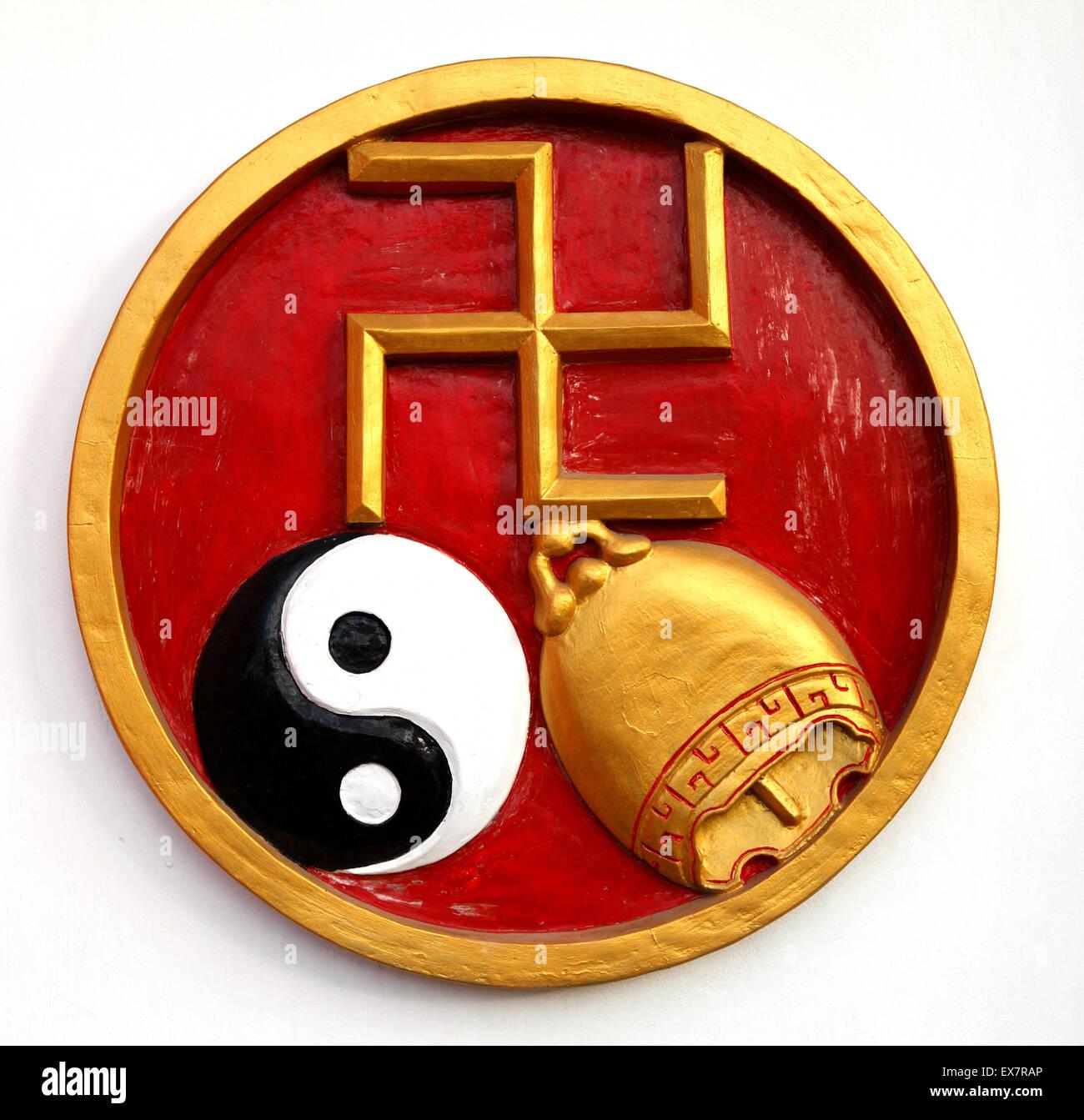 Una decorazione murale di Bali, con una svastica dorata, un Ying e Yang una campana dorata. Si tratta di un simbolo Immagini Stock