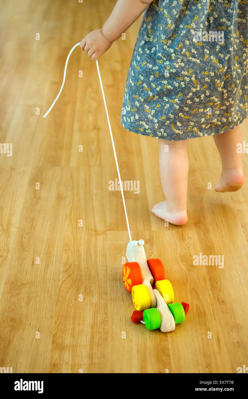 Baby girl tirando un giocattolo di legno Immagini Stock