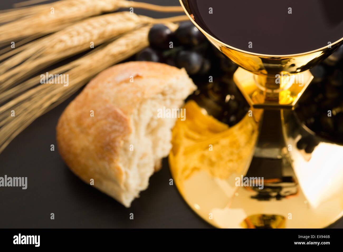 Offerta religiosa, il cristianesimo, oro calice con il vino, uva, pane e le colture Immagini Stock