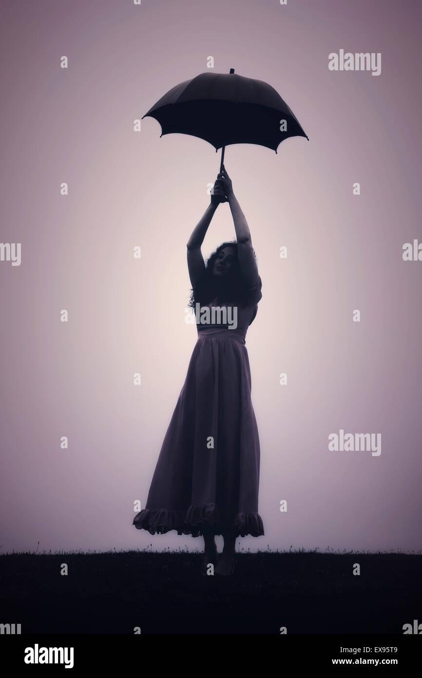 Silhouette di donna con un ombrello Immagini Stock