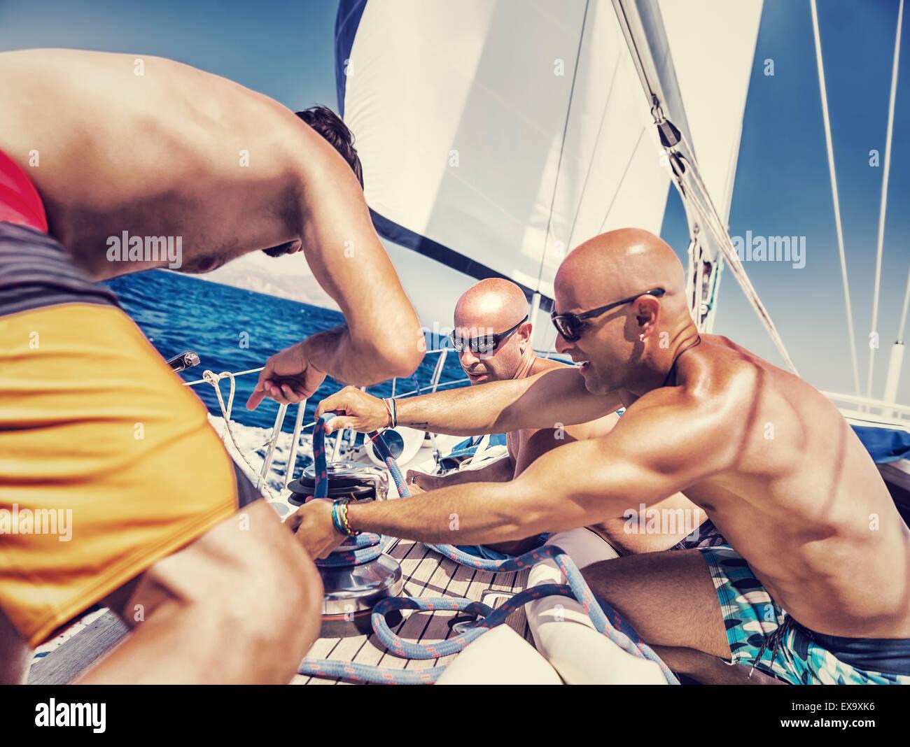 Gruppo di bello shirtless marinai lavorando su barche a vela, coinvolti in concorrenza marittima, godendo di sport Immagini Stock