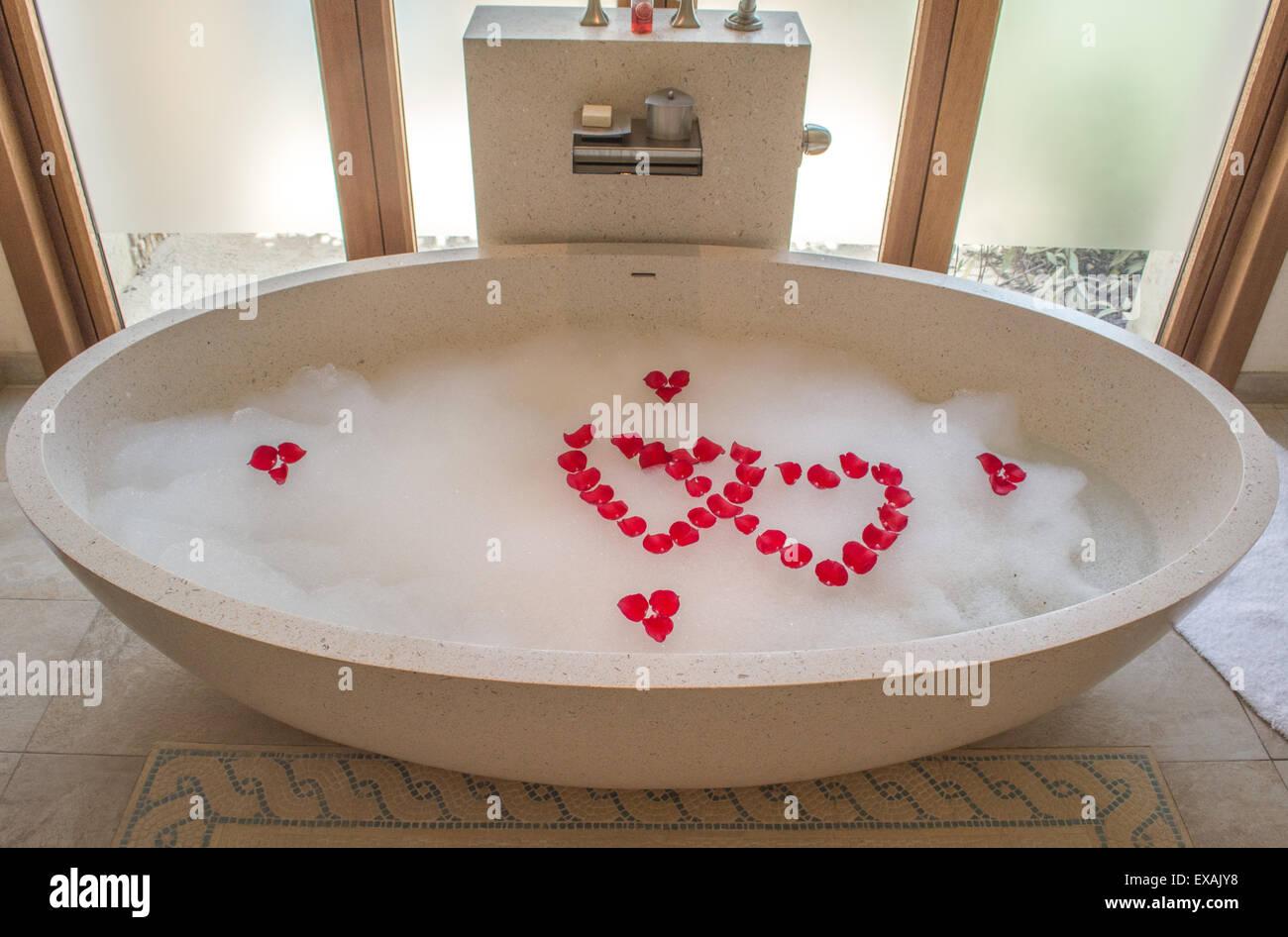 Bagno Romantico In Due bagno romantico con vasca che è riempito con bolle e rose in