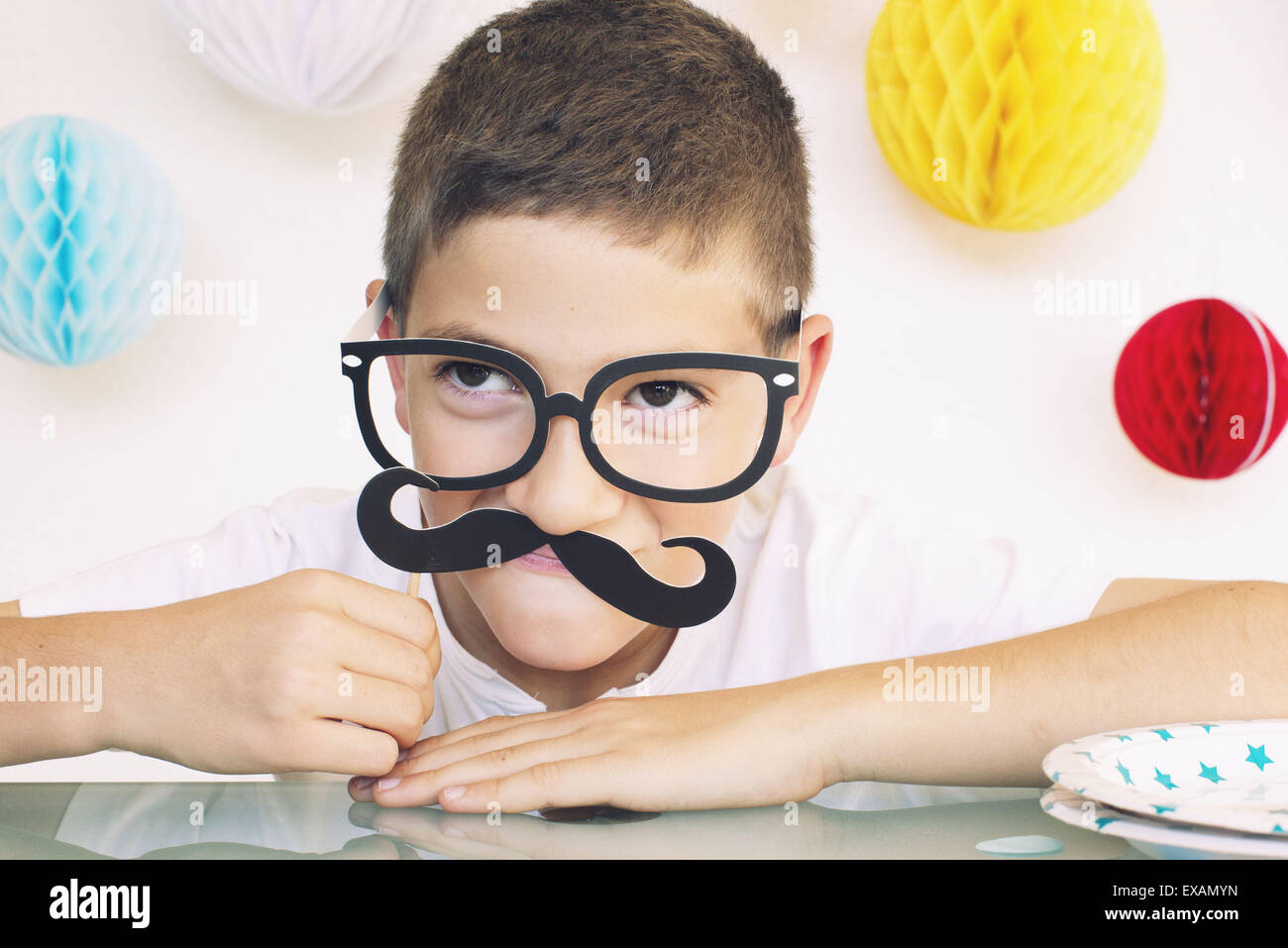 Ragazzo che indossa gli occhiali finti e i baffi a una festa di compleanno, ritratto Immagini Stock