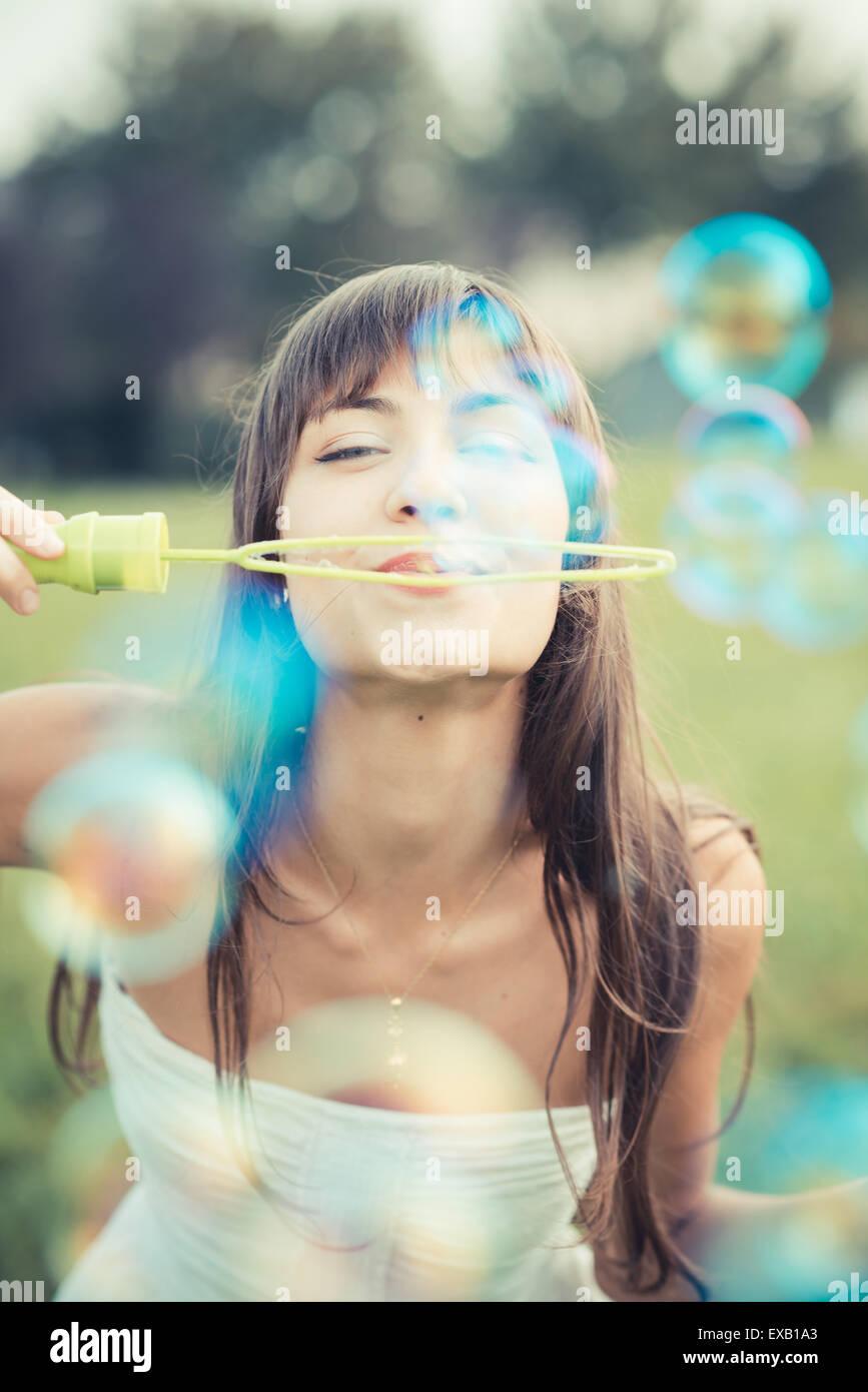 Bella giovane donna con abito bianco di soffiaggio in bolla la città Immagini Stock