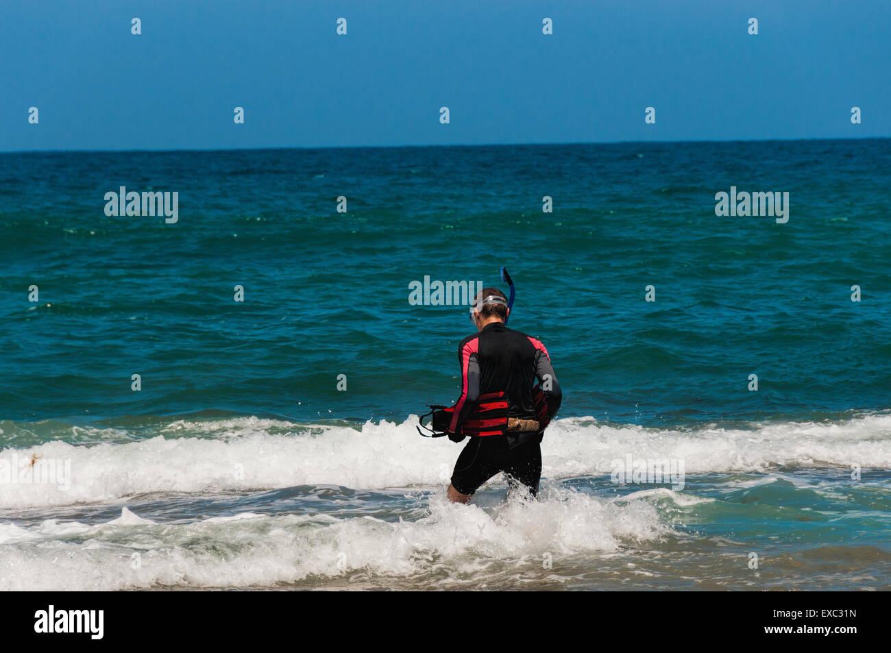 Il subacqueo è andato in mare e vuole mettere sulle pinne e acqua di immersione Immagini Stock