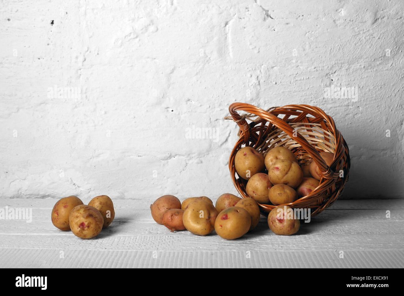 Cestino con patate su vecchie tavole bianco uno sfondo Immagini Stock