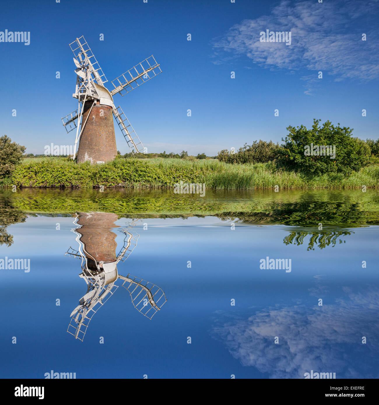 Turf Fen Winmill riflettendo in acque liscia del Norfolk Broads, Norfolk, Inghilterra Immagini Stock