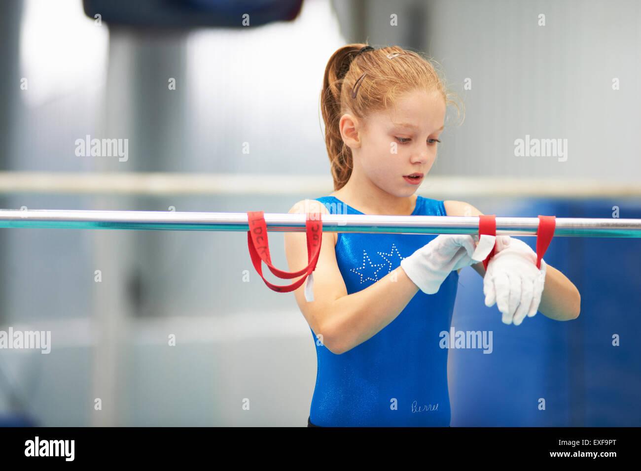 Ginnasta giovani mediante training cinturini da polso per prassi di aiuto su barre Immagini Stock