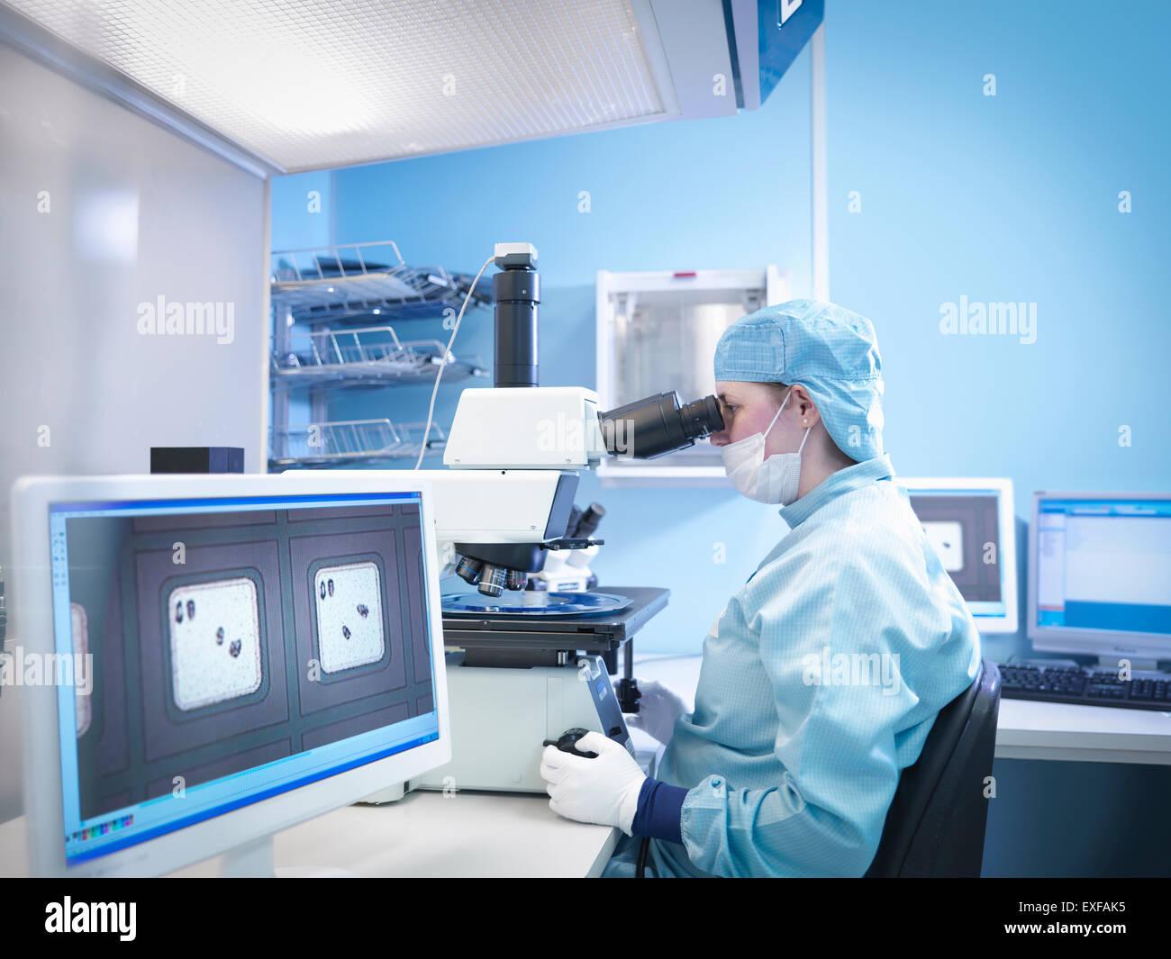 Electronics lavoratore lavora con microscopio nella stanza pulita Immagini Stock