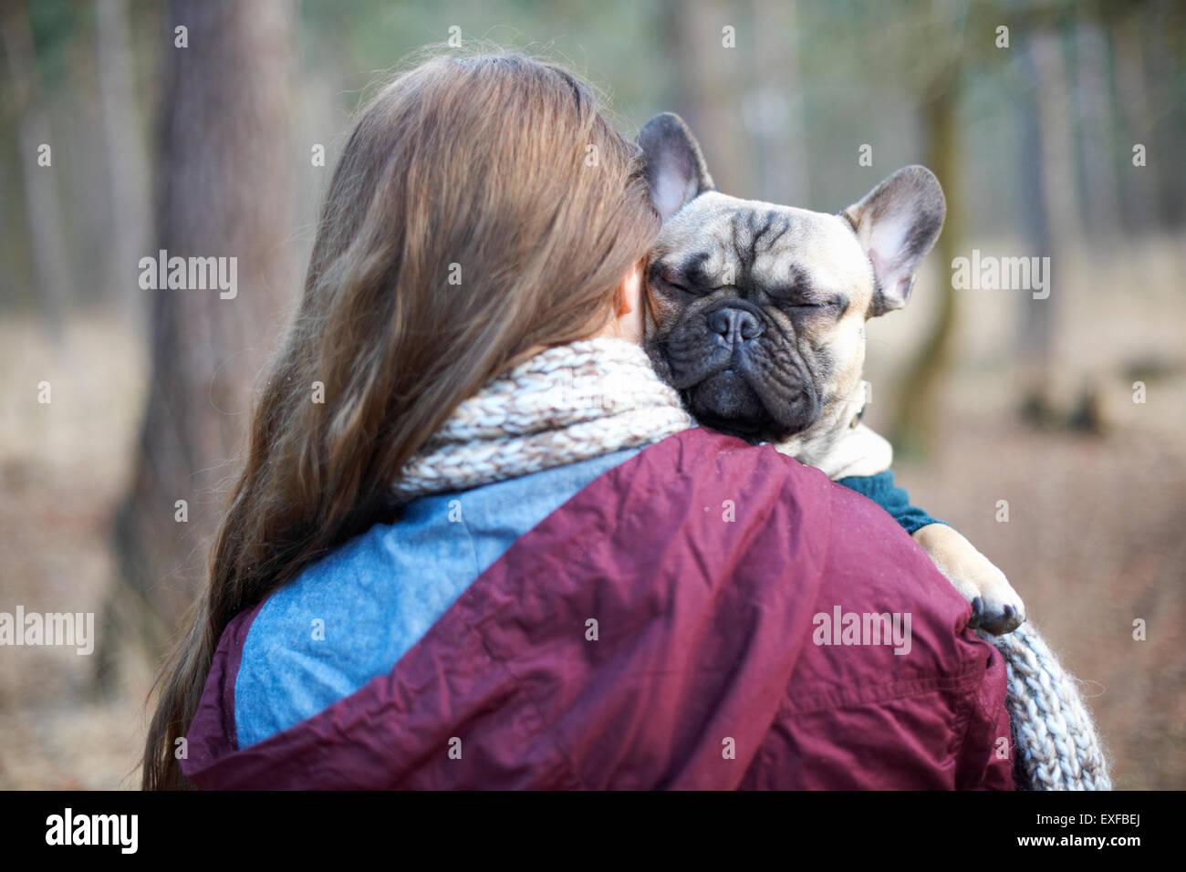Ritratto di cute cane trasportato attraverso la foresta da giovane donna Immagini Stock