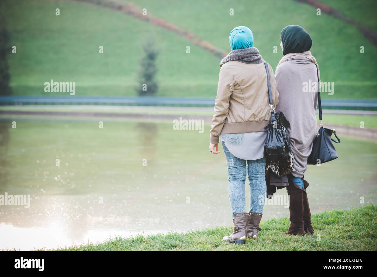 Vista posteriore di due giovani donne guardando fuori dal lago Immagini Stock