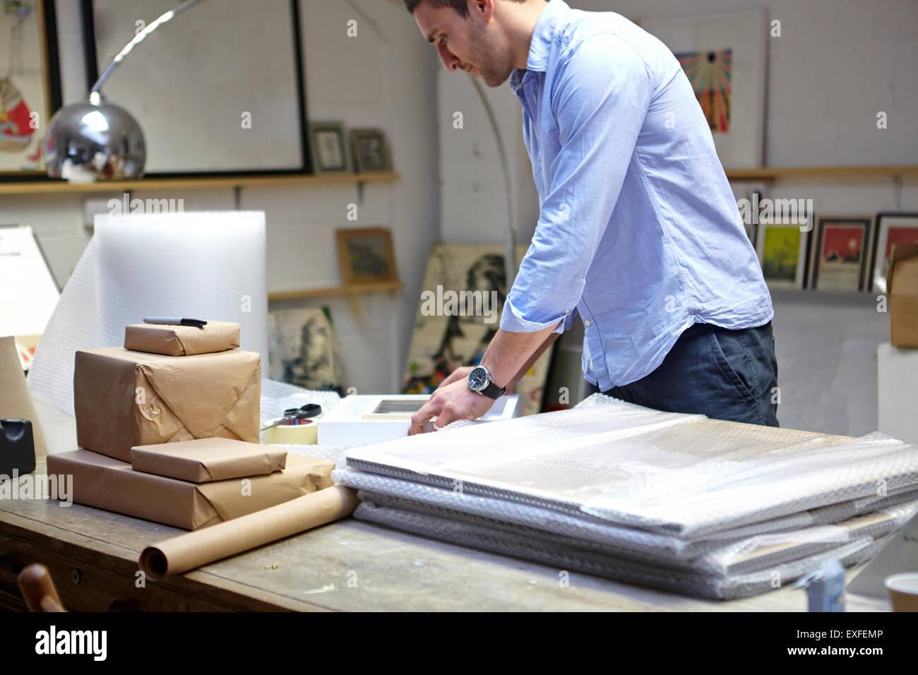 Uomo telai di incarto in Bubble Wrap su tavola in picture corniciai workshop Immagini Stock