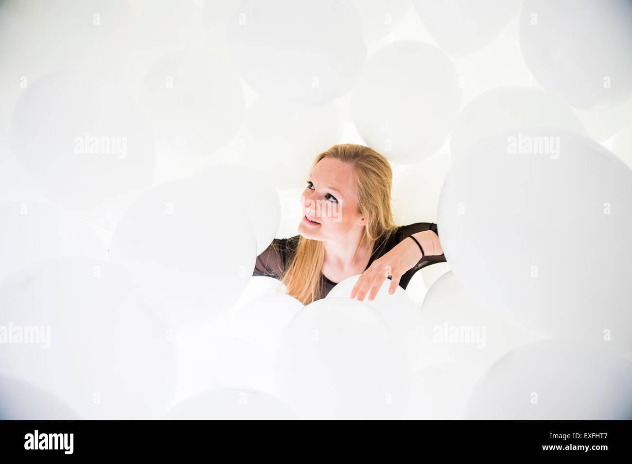 Globophobia: una giovane donna bambina da sola in una nuvola di centinaia di palloncini bianchi aventi superare Immagini Stock