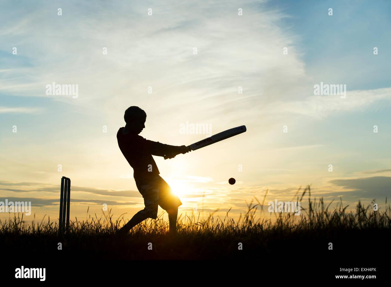 Silhouette di un giovane ragazzo a giocare a cricket contro un sfondo al tramonto Immagini Stock