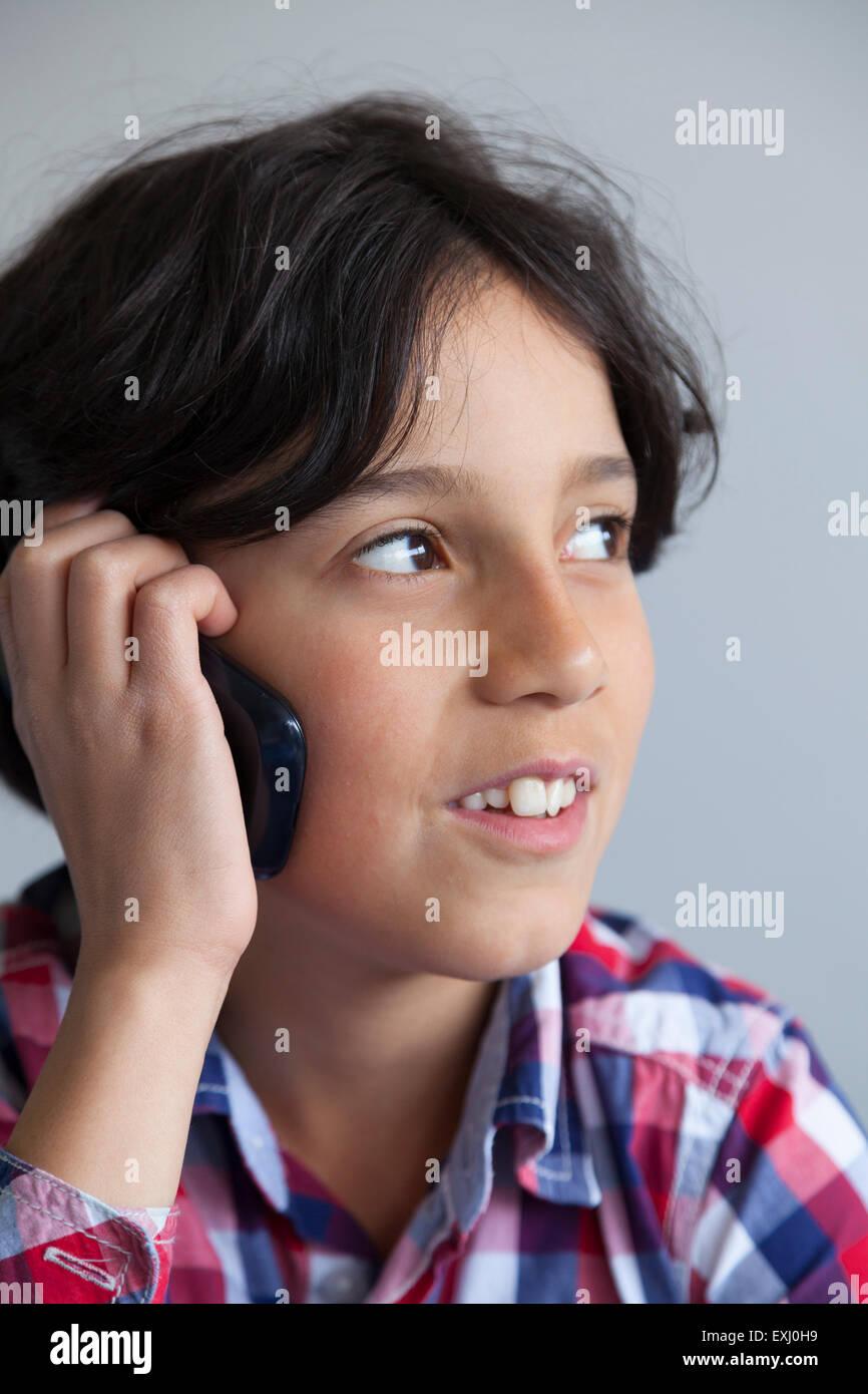 Grave ragazzo adolescente con il suo telefono cellulare Immagini Stock